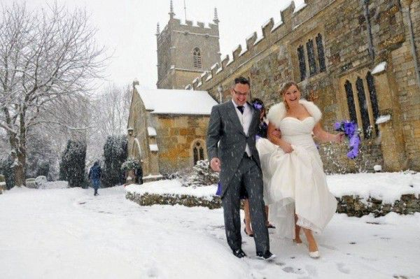Wedding couple outside snowy Cotswold church