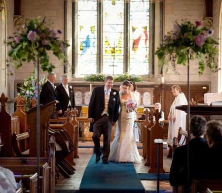bride and groom walk down aisle of country church