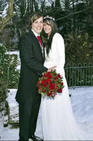 bride and groom at snowy wedding with red bouquet