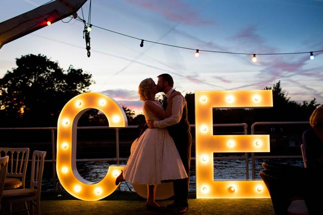 Bride and groom in front of light-up letters Wedding Timings: What Time of day is Best for my Wedding?