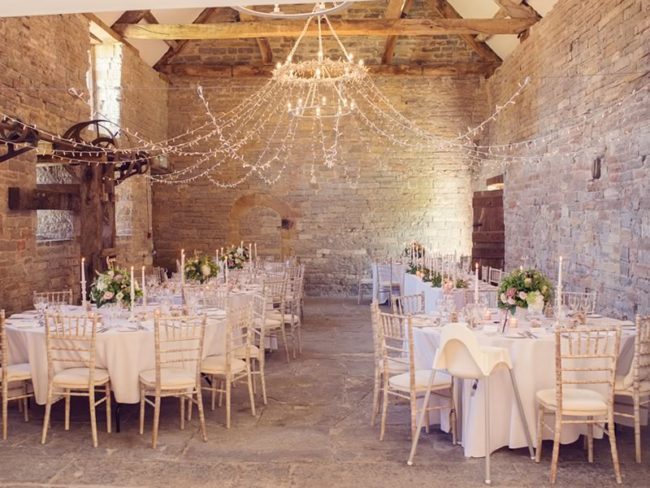 Room view with tables and chandeliers - Barn Wedding Decor and how to Style It
