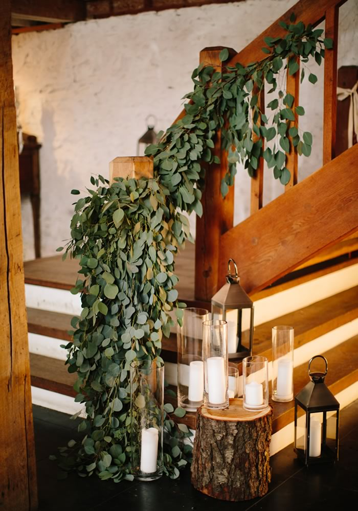 rustic wedding setting, tree trunks with lanterns and greenery winter wedding decorations