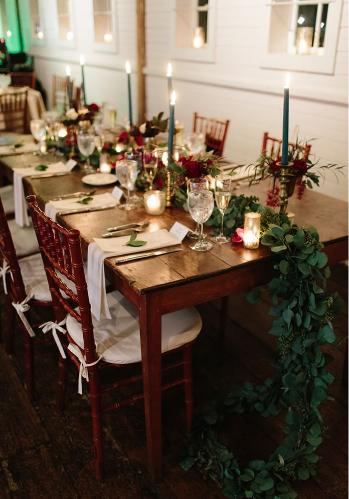 festive table setting with tapered candles and leaf green runner winter wedding decorations