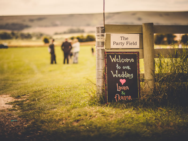 Fire dancing, crackling roasts round the fire and a Campervan bar played centre stage for this homespun outdoor Sussex ceremony of Laura & Fraser!