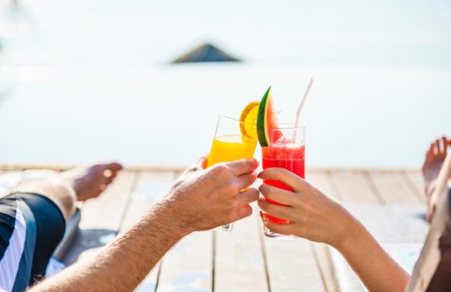Couple drinking cocktails - 6 Money-Saving Tips for Planning Your Honeymoon