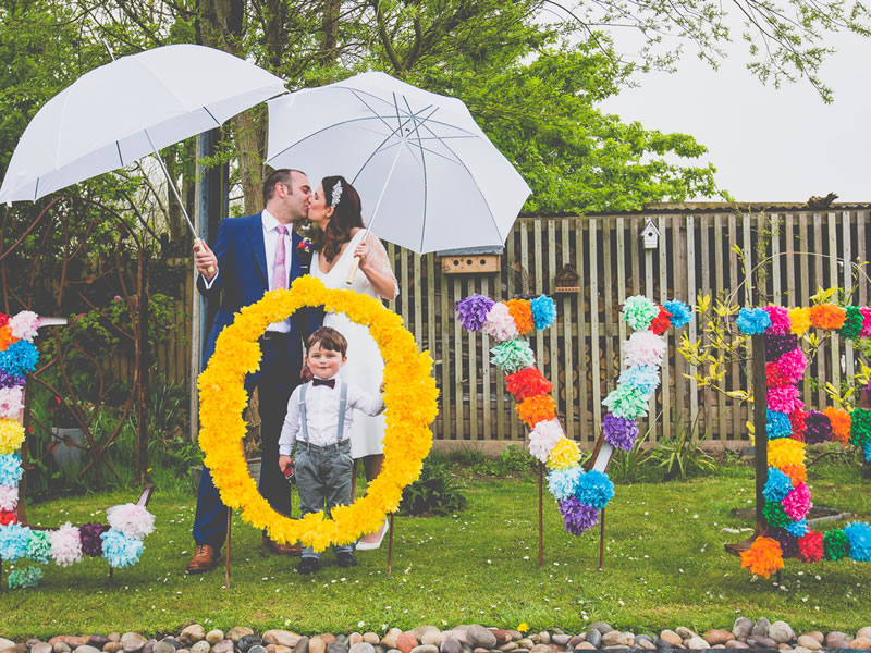 Kissing newlyweds behind LOVE sign Intimate Wedding Venues for Small Weddings