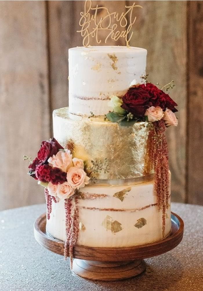 Three-tier gold wedding cake with red flowers