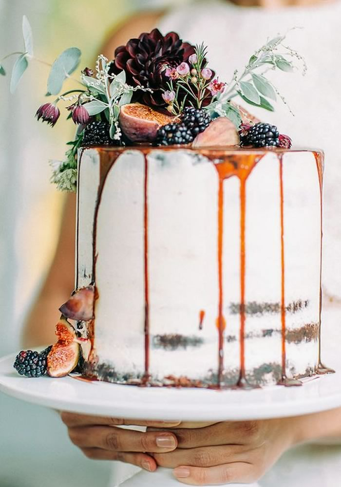 Cream drip wedding cake with figs, blackberries and foliage