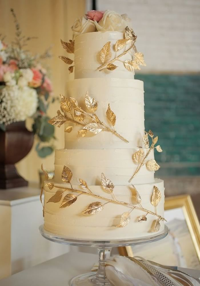Cream wedding cake with gold foliage