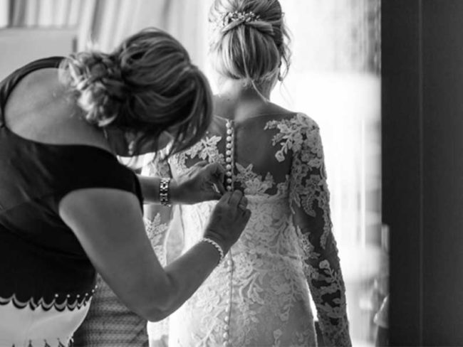 buttoning up the wedding dress choosing the right wedding photographer