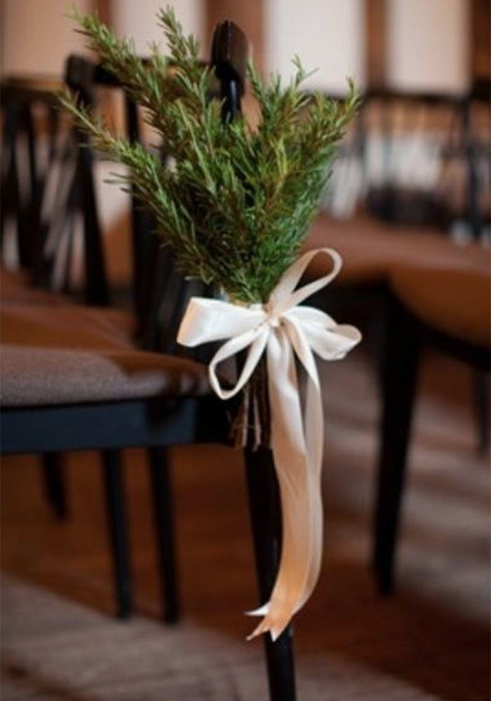 hand tied fir tree leaves and ribbon on a chair for wedding decorations