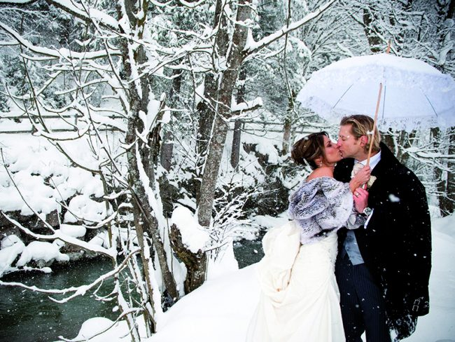 kissing couple at snowy wedding Decorate Your Winter Wedding With these Decorative Ideas