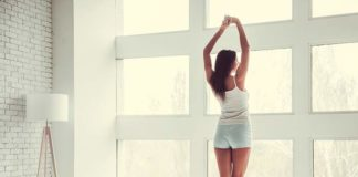 Woman stretching in her bedroom