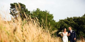 Bride and groom walk through field Wright Wedding Photography