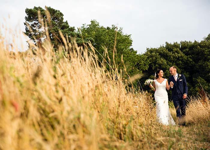 Bride and groom walk through field Wright Wedding Photography