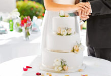 bride-groom-cutting-white-wedding-cake-three-tiers
