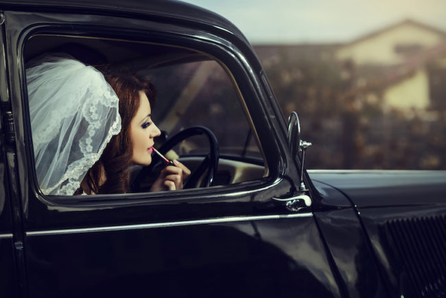 bride-doing-lipstick-in-wedding-car-best-bridal-makeup-products-for-your-wedding-day