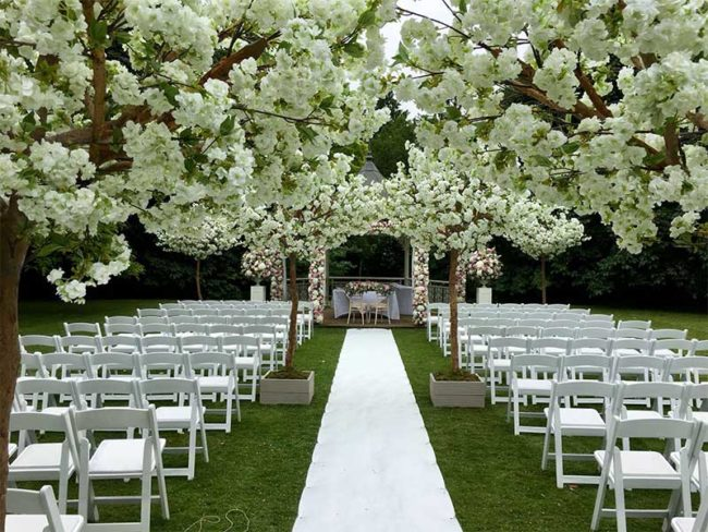 blossom trees lining outdoor wedding aisle dressing your wedding venue with artificial trees