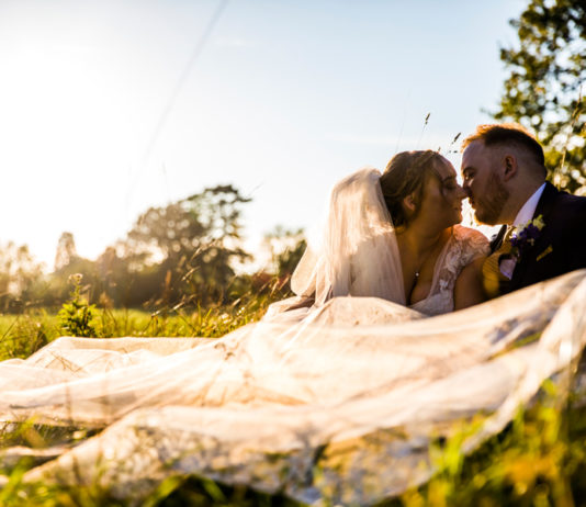 Bride-and-groom-sitting-on-grass