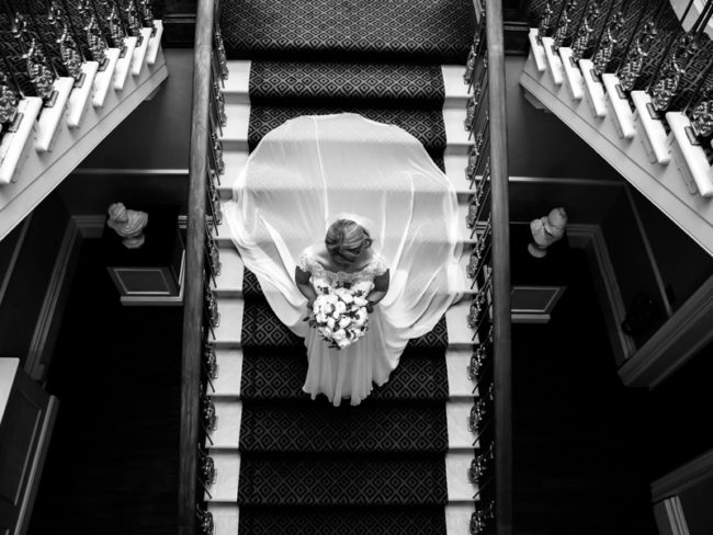 Bride walks down stairs from above Win a £500 Voucher and Photo Booth From Wright Wedding Photography